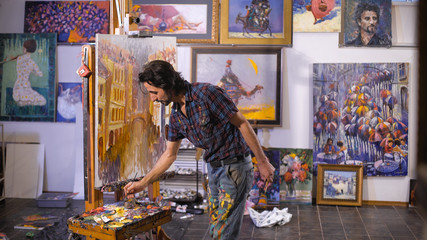 Inspiration. Colorful professional artist paints with oil. Workshop