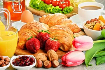Breakfast consisting of croissants, coffee, fruits, orange juice