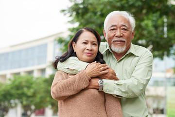 Portrait of hugging senior Vietnamese couple