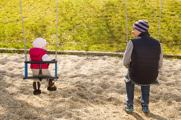Mann sitzt mit seiner Tochter auf einer Schaukel auf einem Spielplatz