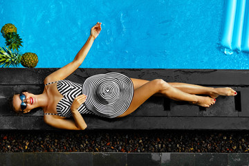 Woman Summer Fashion. Happy Sexy Smiling Girl With Fit Body, Long Legs, Healthy Skin In Bikini, Sun Hat, Sunglasses Sunbathing By Swimming Pool On Travel Holidays Vacation. Beauty, Wellness, Lifestyle Wall mural