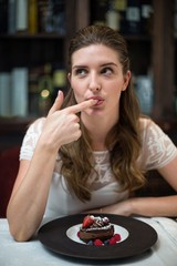 Thoughtful woman tasting desert