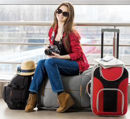 young attractive woman in a red jacket and sunglasses sitting on suitcases in the terminal or train station.