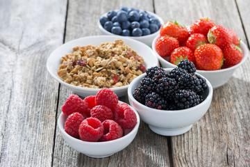 garden berries and muesli on wooden background