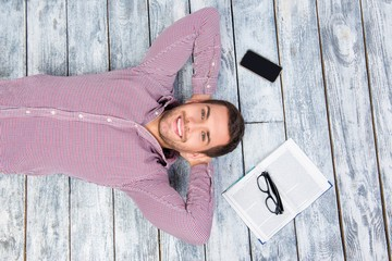 Top view photo of smiling man  lying on the floor with book, phone and glasses