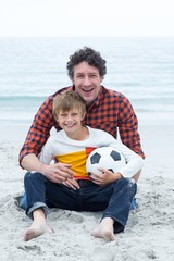 Father and son holding soccer ball while sitting at beach