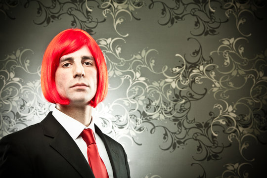 businessman with colored tie and hair wig on tapestry background