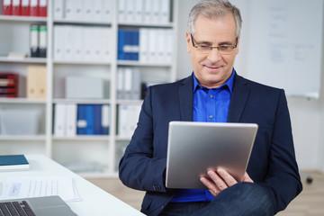 älterer geschäftsmann sitzt am schreibtisch und schaut auf tablet-pc