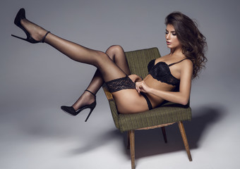 Beautiful sexy lady in elegant black lingerie and stockings. Bea