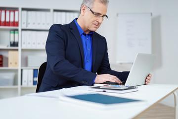 manager arbeitet konzentriert am laptop