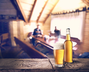 Bottle and glass of beer on table