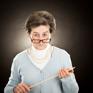 old strict teacher with glasses isolated on black