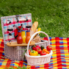 Picnic on the grass. Picnic basket with vegetables and bread. A