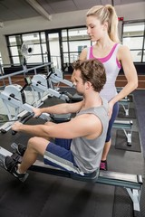 Female trainer assisting a man on rowing machine