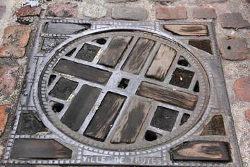 plaque d'égout fonte et bois