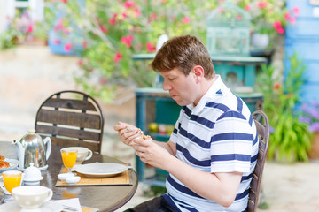 young man having breakfast outside in summer with various jams,
