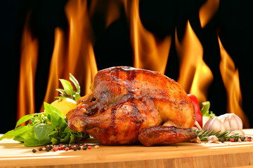 Roast chicken and various vegetables on a chopping wood