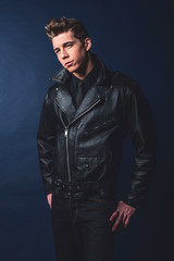 Cool vintage rock and roll 50s fashion man wearing black leather
