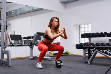 Woman doing squat exercise at gym