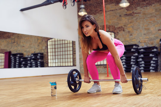 Young woman doing deadlift exercise with barbells at gym