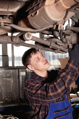 Car mechanic inspecting car wheel and suspension detail of lifte