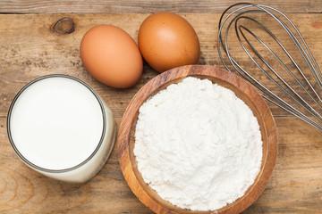 Eggs,flour, milk on a wooden worktop