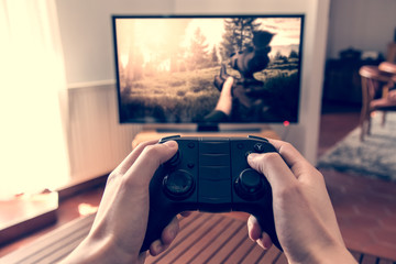 Playing game on console - hands holding game pad and playing shooter game on tv screen.