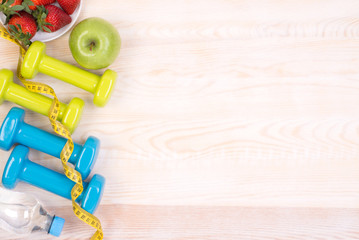 Fitness equipment on wooden background with copy space