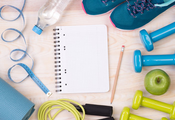 Fitness equipment and blank notebook on wooden background