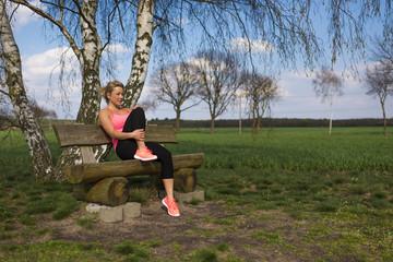 Blonde Joggerin sitzt draussen auf einer Bank und ruht sich aus