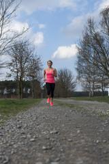 Junge Frau in Sportkleidung joggt auf einem Schotterweg