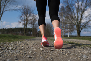 Frauenfüße in Turnschuhen joggen auf einem Schotterweg