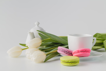 Three macaroons, cup of coffee and white flowers tulip