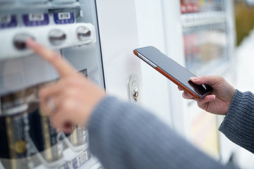 Woman using cellphone to pay the vending machine
