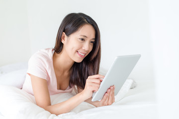 Woman use of tablet pc and lying on bed