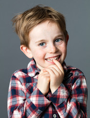 portrait of a shy red hair 5-year old boy smiling and biting his teeth for childhood and wellbeing, grey background studio