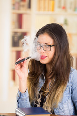 Brunette wearing glasses and bright lipstick vaping, smoking e-cigarette with smoke visible