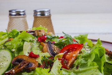 vegetable salad - cold appetizer of fried mushrooms with lettuce and tomatoes