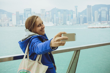 Young woman makes the photo on the phone dressed in a fashionabl