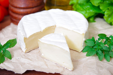 Brie cheese. Camembert cheese. Fresh Brie or Camembert cheese with basil leaves. Italian, French and Mediterranean ingredients.