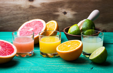 Fresh citrus juice and fruits on wooden background
