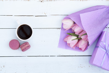 Beautiful bouquet of pink tulips in violet paper, gift, cup of coffee and two pink macaroons on light wooden background