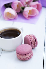 Cup of coffee and two pink macaroons on light wooden background