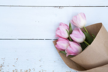 Beautiful bouquet of pink tulips in paper on light wooden background