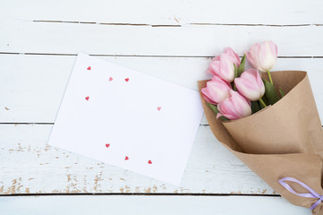 Beautiful bouquet of pink tulips next to a white envelope and pink sugar hearts on light wooden background