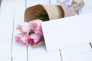 Beautiful bouquet of pink tulips next to a white envelope on light wooden background
