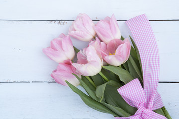 Beautiful bouquet of pink tulips on light wooden background
