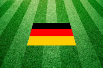 Sunny artificial green soccer or rugby grass with Germany flag background. Selective focus used.