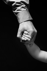 Father's hand holding child's hand. Hand businessman in shirt holding a child's hand. Isolated on black background. Grayscale.