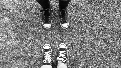 Pair of legs in black and white sneakers